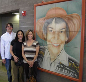 Family of Martha Cooper poses next to mosaic of Martha Cooper