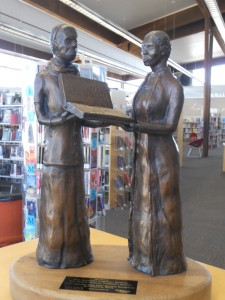 Margaret Campbell (L) gives Quincie Douglas (R) a copy of her book Iba, The Dawn. Bronze sculpture by Richard Quin Davis