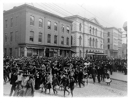 Photo of several hundred African Americans dressed up and parading down a city street for Juneteenth.