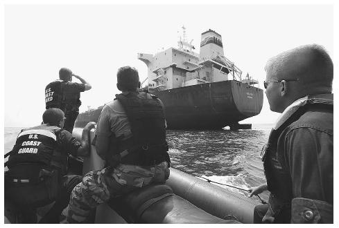 photograph of three members of the US Coast Guard in a boat with a large shipping vessel in the background