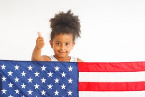 Little girl showing thumb up. American flag on the front