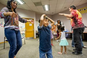 boy and mom dance with other kids at rainbow storytime