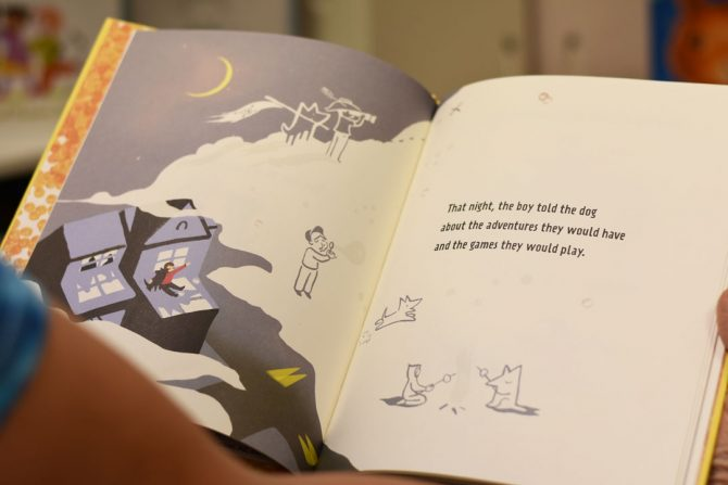 toby displays a page from the book Hey Boy
