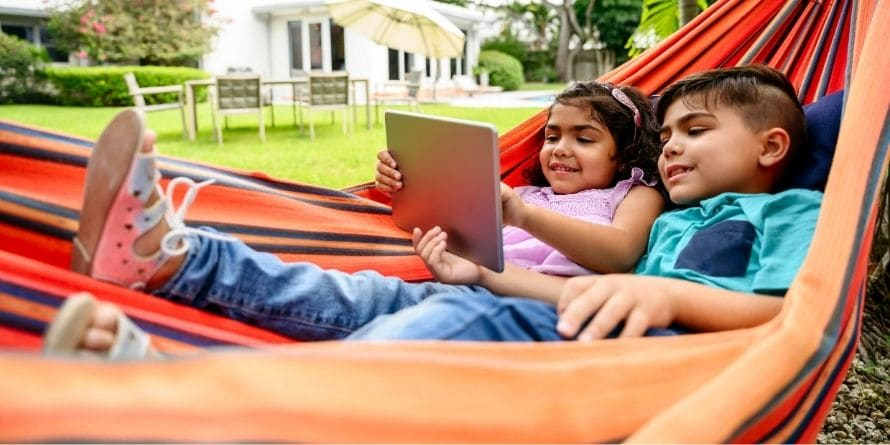 latinx boy and girl children kids reading on a tablet lying in a hammock