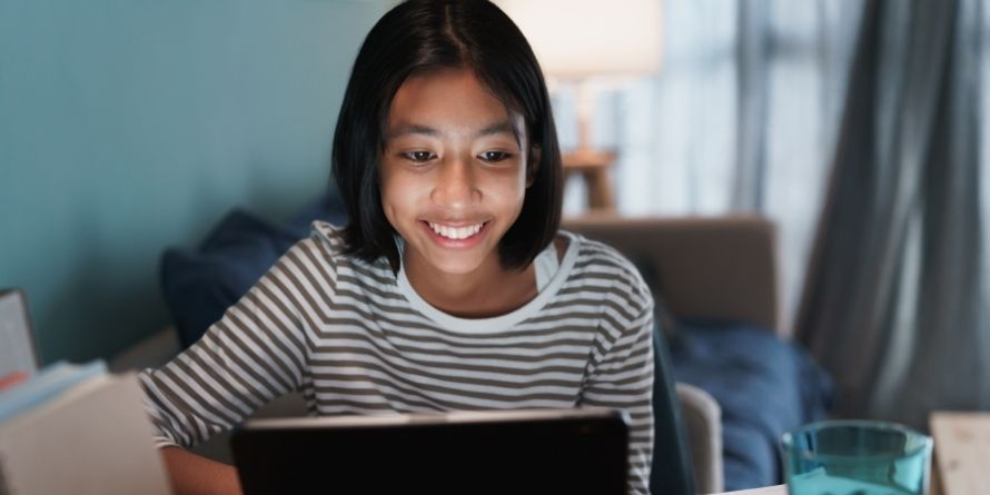 young teen female girl on laptop smiling - used for virtual volunteer - rectangle
